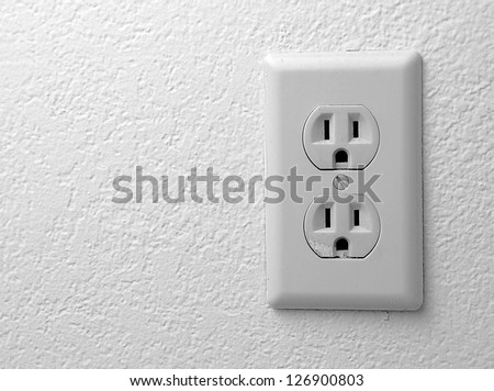 Electric outlet on the wall covered with wallpaper.