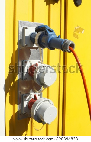 electric outside sockets with cable and yellow background