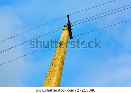 Electric pillar with wires on sky background