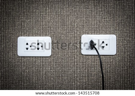 Electric plug and power outlet on gray background - stock photo