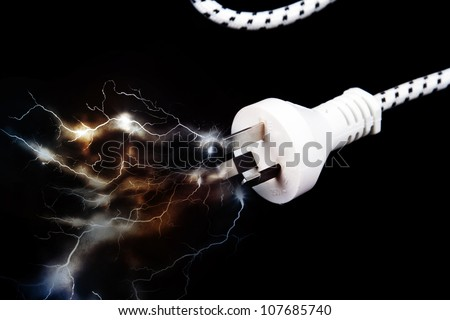 Electric plug on black with sparks - stock photo