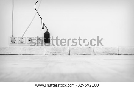 Electric plugs in a socket in the white interior - stock photo