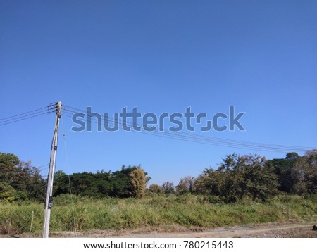 Electric pol at country road with grass ,green tree and clear blue sky