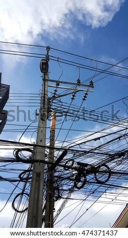 Electric pole and disorder wire with beautiful blue sky in background.
