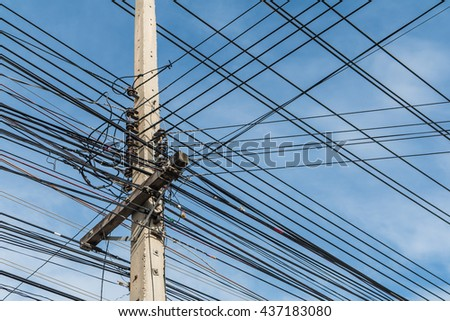 Electric pole and disorganized, messy electricity line with against blue cloudy sky, abstract background. - stock photo