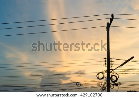 Electric pole connect to the high voltage electric wires on sunset sky background. - stock photo
