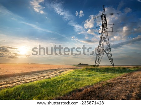 Electric pole in the autumn field at sunrise - stock photo