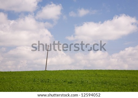 Electric pole in the green meadow against cloudy sky