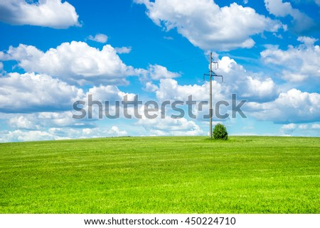 Electric pole on a green field and cloudy sky. Country landscape