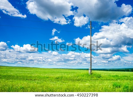 Electric pole on a green field. Country landscape