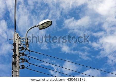 Electric pole with lamp on blue sky with clouds background