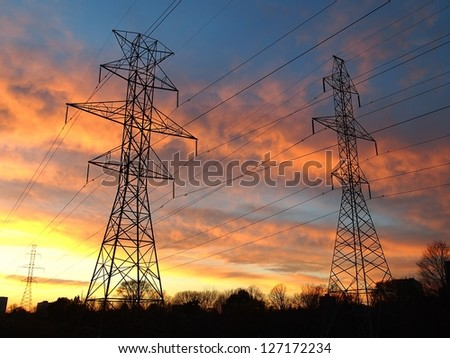 Electric post in a field and colorful sky - stock photo