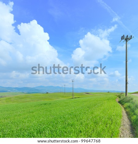 Electric power line pylons in a green field and a light cloudy blue sky in spring season.Tuscany, Italy. - stock photo