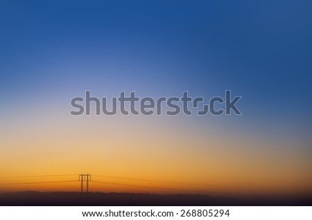 Electric power line with pylons on colorful evening sky