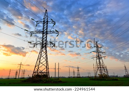 Electric power lines against sky at sunrise - stock photo