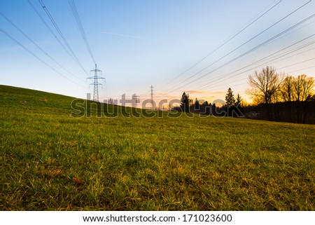 Electric power lines and pylons at sunset with green grass in foreground - stock photo