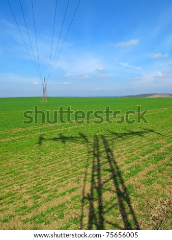 Electric power lines on green field.