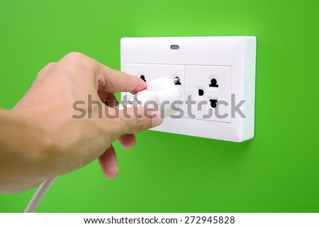 Electric power plug in a hand and inserting into power wall socket - stock photo