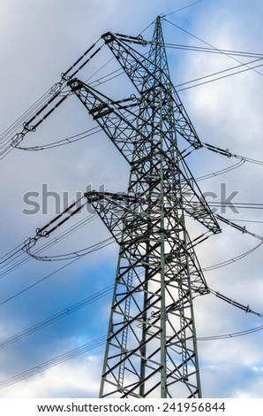 electric power pole in front of blue sky - stock photo