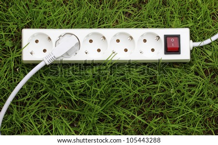 electric power receptacle and plug on the grass, energy concept - stock photo