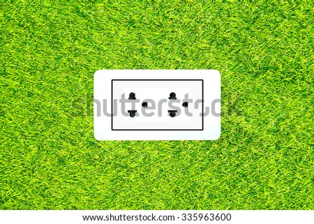 Electric power receptacle on a green grass surface background - stock photo