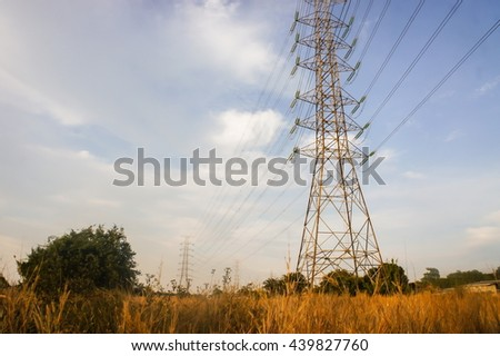 Electric power station in the field in blue cloudy sky - stock photo