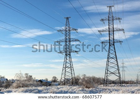 Electric power transmission in the field in the winter against the blue sky - stock photo