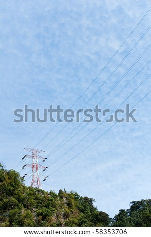 electric pylons and wires up in the mountains - stock photo