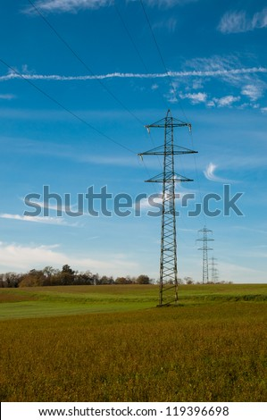 Electric pylons in a blue sky and green fields