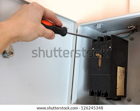 electric repairs an electric switch - stock photo