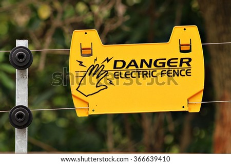 Electric safety fence with danger sign. Security. - stock photo
