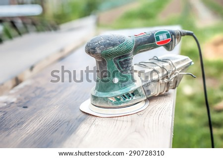 Electric Sander. Carpenter sanding a wood with sander, outdoors - stock photo
