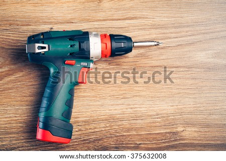 electric screwdriver on wooden background - stock photo