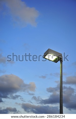 Electric Street lamp in the park, sky with clouds at the sunset. - stock photo