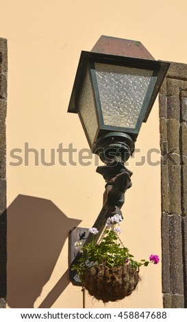 Electric street lamp on wall of building in Funchal, Madeira, Portugal