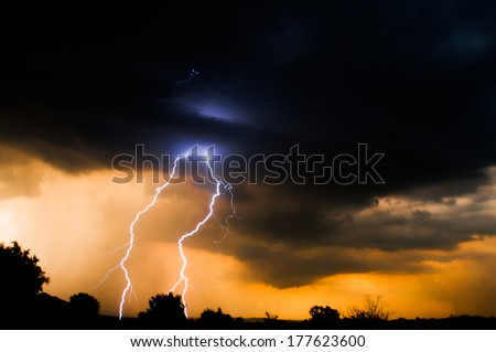 Electric Sun Set with lightning from clouds as the sun sets - stock photo