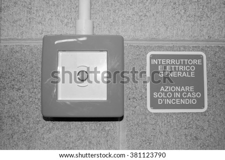 Electric switch with label in Italian meaning Electric Switch - Press in case of fire in black and white