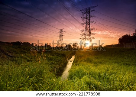 Electric tower at sunset with sun.  - stock photo
