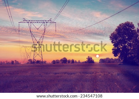 Electric towers on a field with sunrise.  - stock photo
