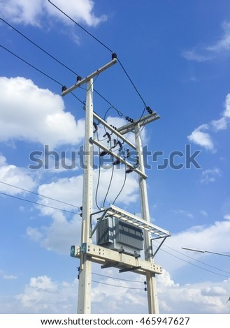 Electric transform on electric pole with blue sky.