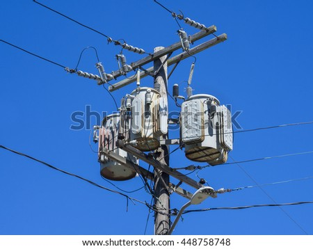 Electric transformer on blue sky - stock photo