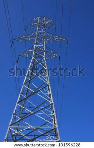 electric transmission tower against the clear blue sky - stock photo
