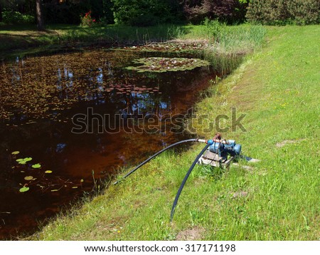 Electric water pump placed on the pond coast.        - stock photo