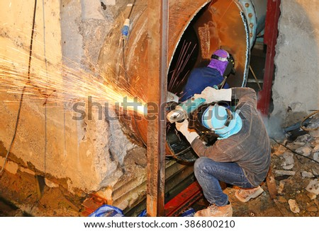 Electric wheel grinding on large steel pipe - stock photo