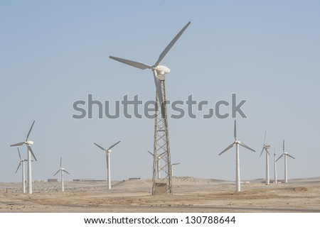 Electric wind turbine generators in the desert against a blue sky background - stock photo