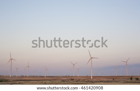 Electric wind turbines farm with sunset light on arid landscape, Spain