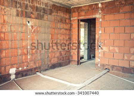 Electric wires and socket installation and pipes of electricity in house construction site.  - stock photo