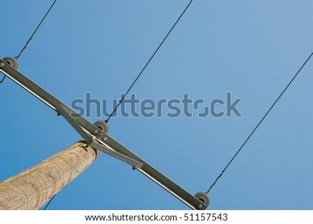 Electric wires and wooden pole on blue sky