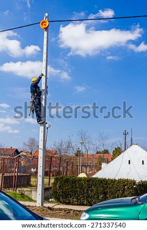 Electric worker is climbing up on a pole - stock photo