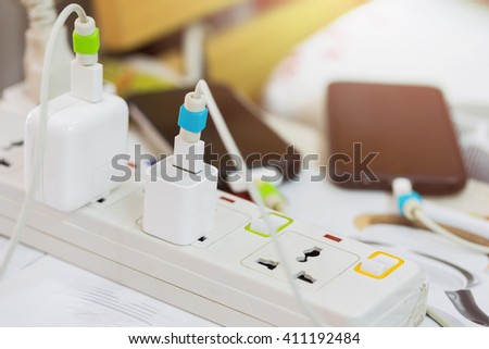 Electrical appliances pluged, several adapter and charger. - stock photo